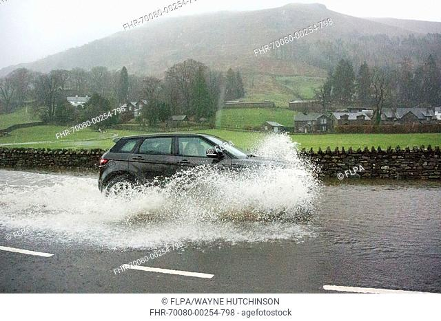 Car driving through floodwater on road during heavy rainfall, A591, Grasmere, Lake District, Cumbria, England, December