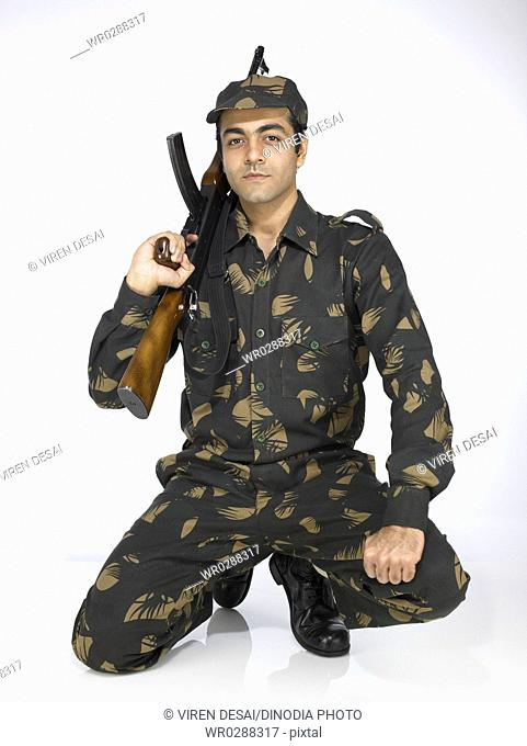 Indian army soldier sitting on knee holding AK-47 gun MR702A