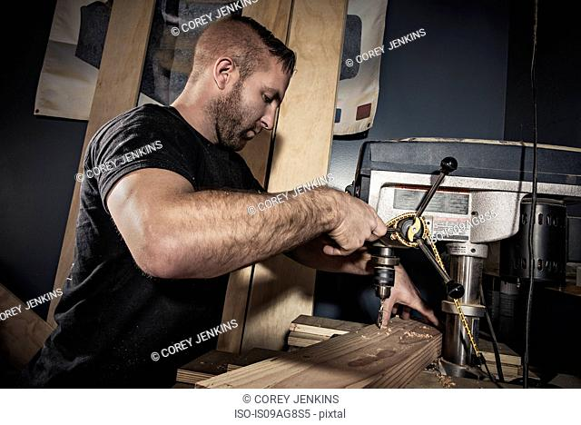 Male carpenter drilling wooden plank in workshop