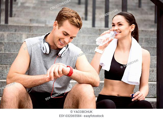 We love running together. Happy young man and charming woman sitting on the stairs after running, young woman drinking water
