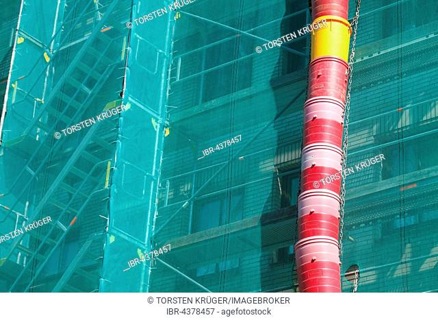 Construction site, downpipe for rubble, façade of building covered in green tarpaulin, city centre, Lübeck, Germany