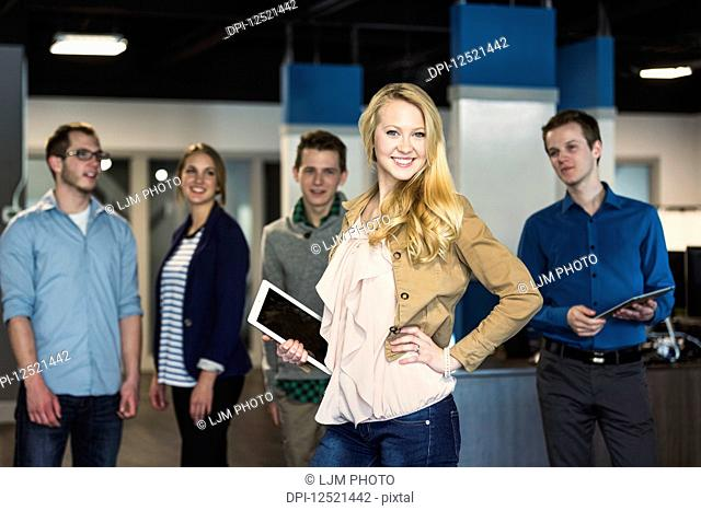 Portrait of a group of young millennial professionals standing together in the workplace; Sherwood Park Alberta, Canada