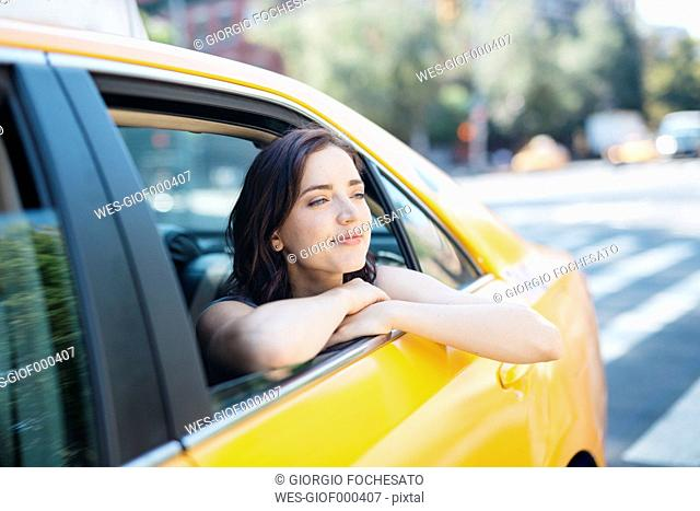 USA, New York City, portrait of young woman leaning out of window of a yellow cab