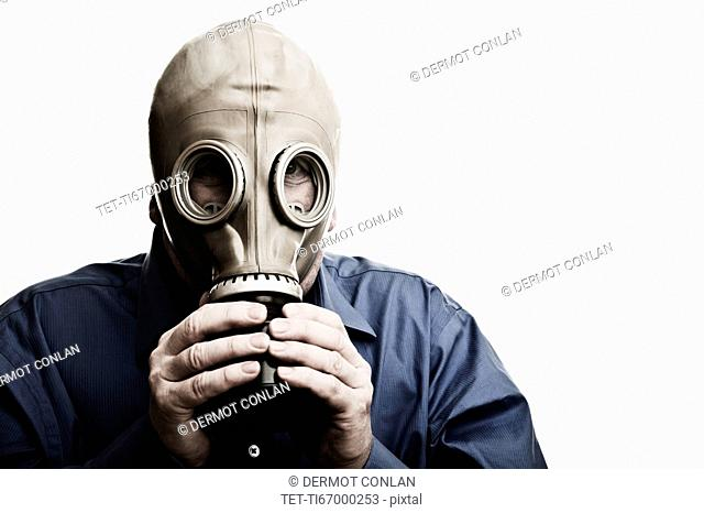 Studio shot of man trying to breath in gas mask
