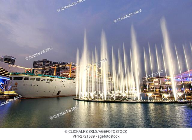 Dancing Fountains in New Sea World Plaza, one of the landmark of Shenzhen, at sunset with the Minghua ship on its center