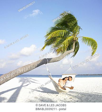 Hispanic couple in hammock at beach