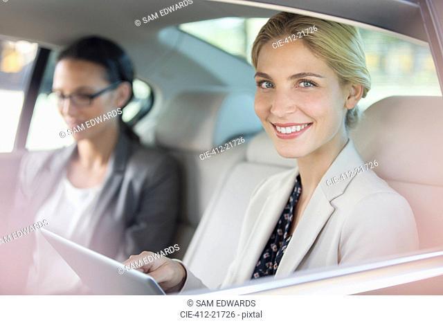 Businesswoman using digital tablet in car back seat