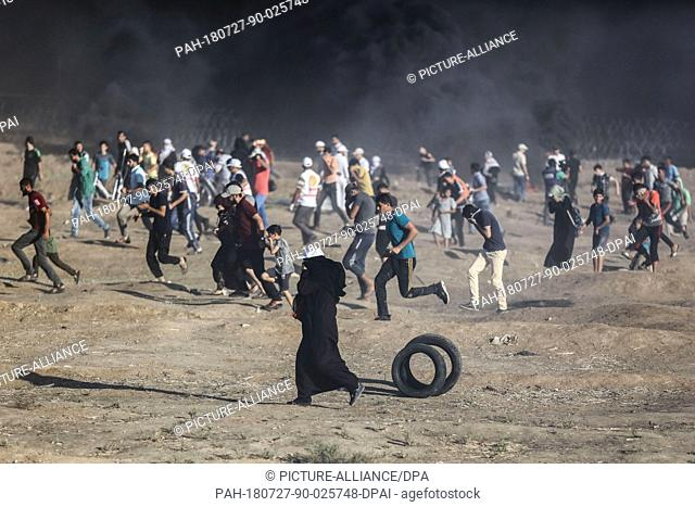 Palestinian protesters run to take cover from tear gas fired by Israeli Security forces during clashes along the Israel-Gaza border, east of Gaza city