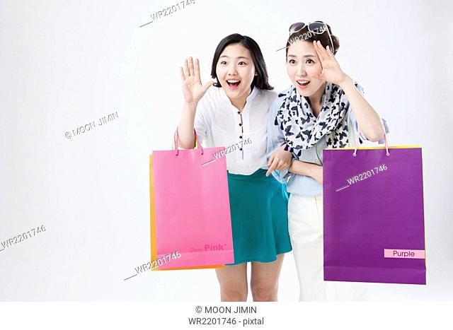 Portrait of mother and daughter holding shopping bags with surprised faces