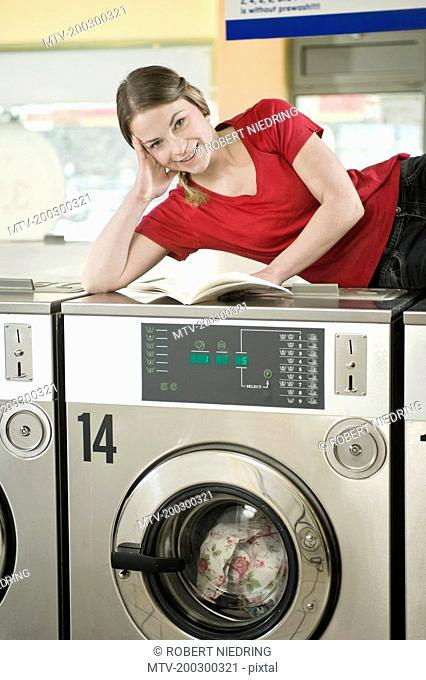 Portrait of young woman reading book on top of machine, smiling