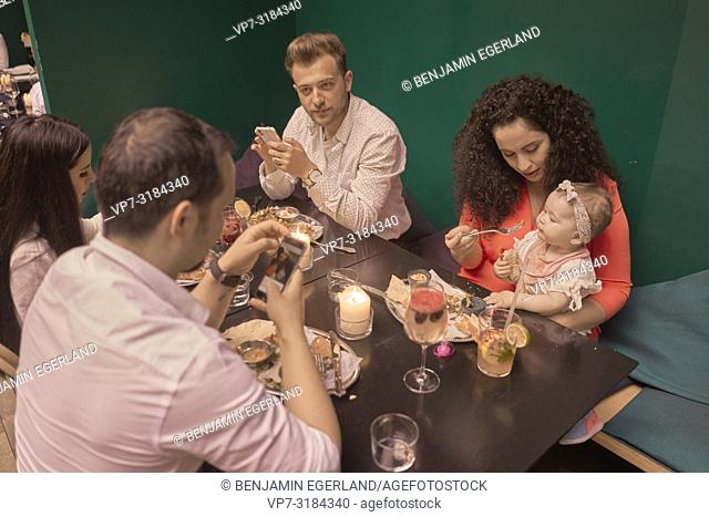 Family eating in restaurant, phone, distraction, Vegan Oriental, Kismet, in Munich, Germany
