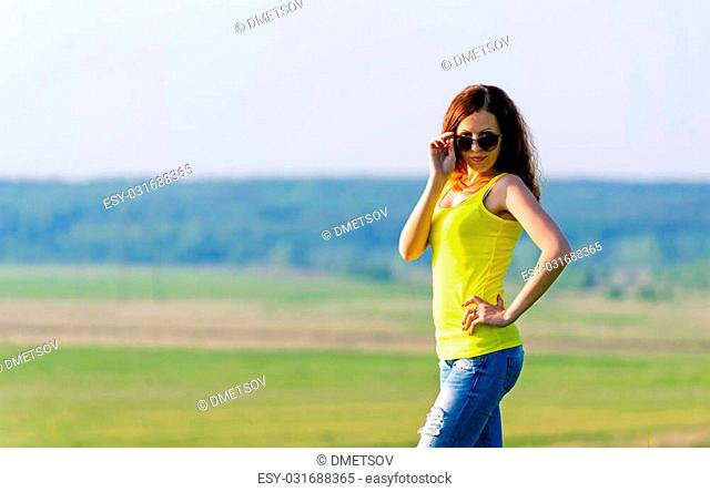 Attractive casual brunette on a beautiful nature looking over her sunglasses