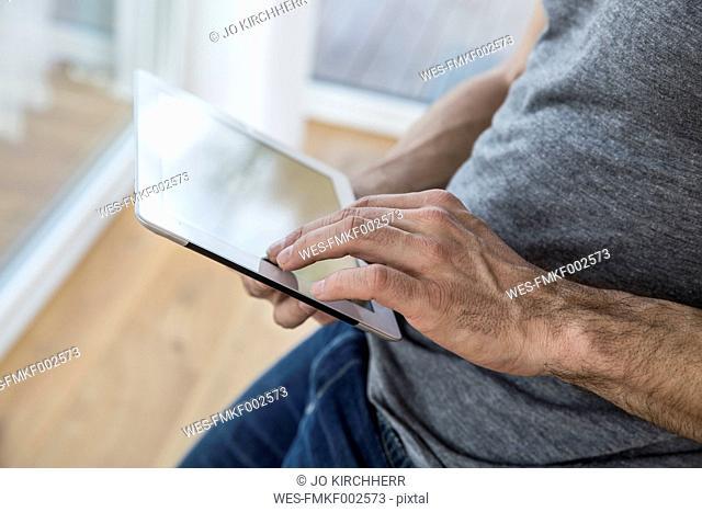 Man at home using digital tablet