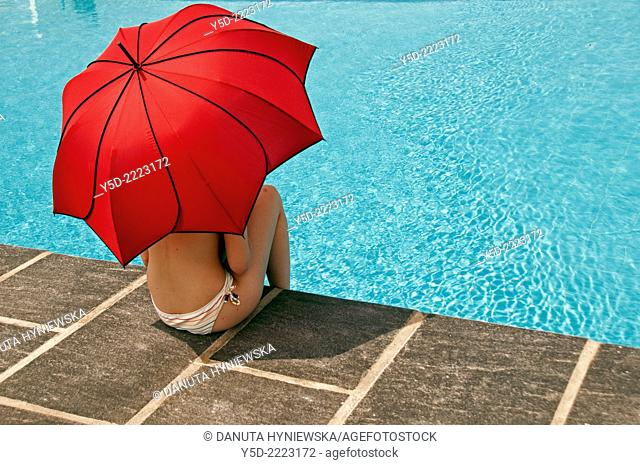 Woman with red umbrella, swimming pool