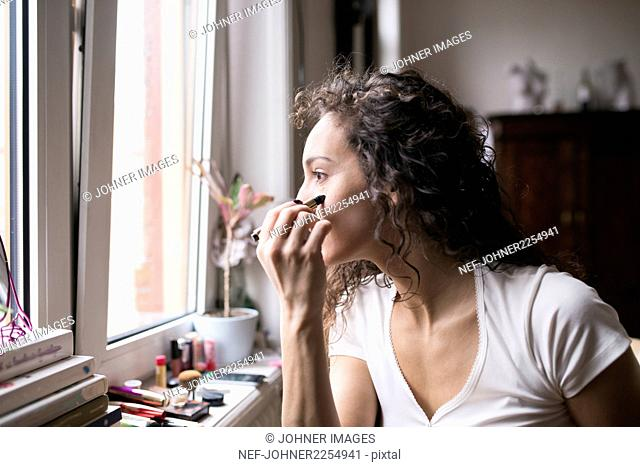 Woman doing her makeup by the window