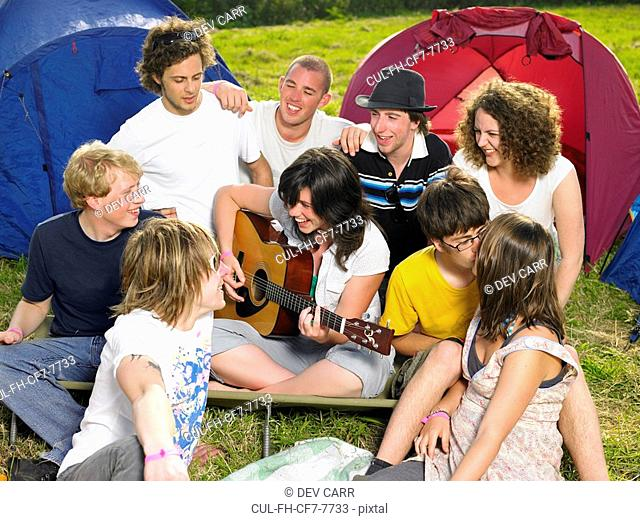 Group outside tent one girl playing a guitar