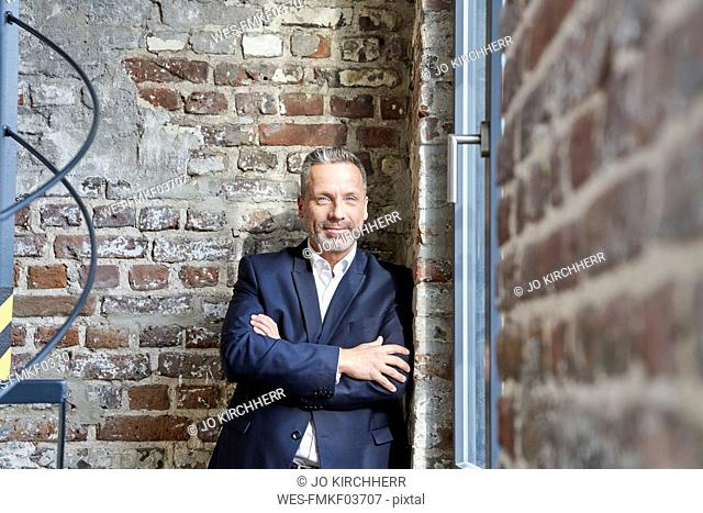 Portrait of confident businessman leaning against a brick wall
