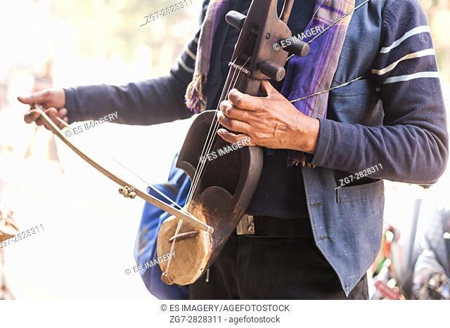 Nepalese street musician playing a Sarangi violin in Pokhara, Nepal