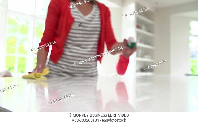Slow motion sequence of woman cleaning kitchen surface with cleaner and cloth. Shot on Sony FS700 in PAL format at a frame rate of 50fps