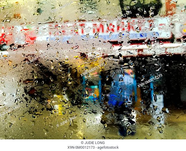 Looking out the rain covered window of a New York City Bus traveling down Ninth Avenue. Meat Market with people walking past in the rain