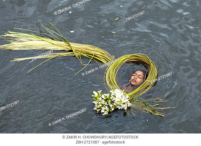 DHAKA, BANGLADESH - AUGUST 05 : A girl swiming taking water lilies from a lake for sell them in market near Dhaka, Bangladesh on August 05, 2016