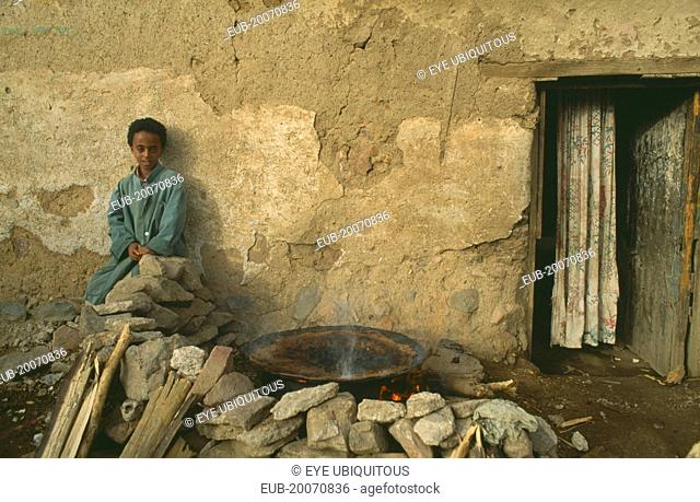 Child sitting outside poor household with injera cooking on open fire at side
