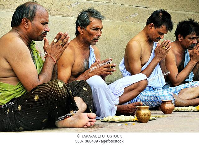 Pilgrims praying at the ghat by the Ganges river