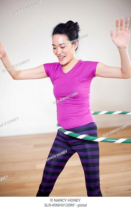 Woman using hula hoop indoors
