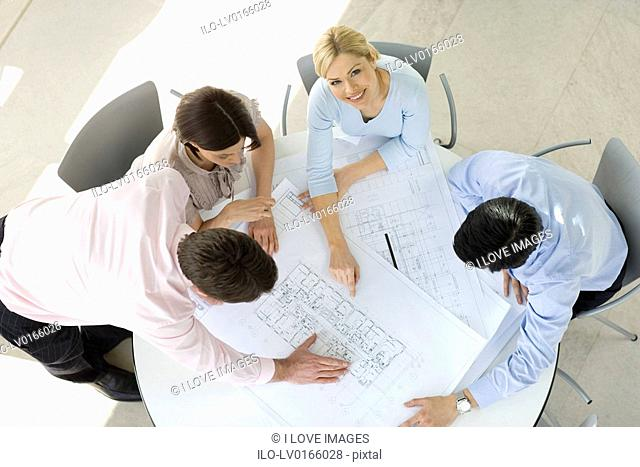 Four colleagues having a meeting, discussing architects plans