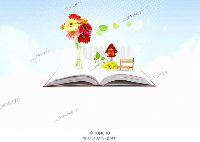 an open book with flowers on top of it