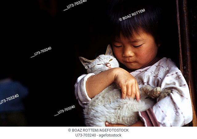 A little girl from the Miao minority holds her sweet cat, China