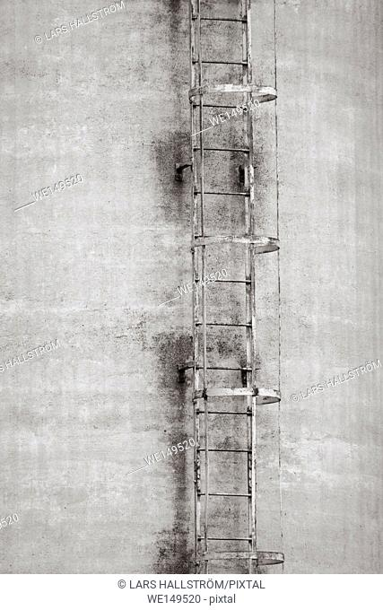 Exterior of old industrial building with ladder. Concrete architecture. Abandoned factory