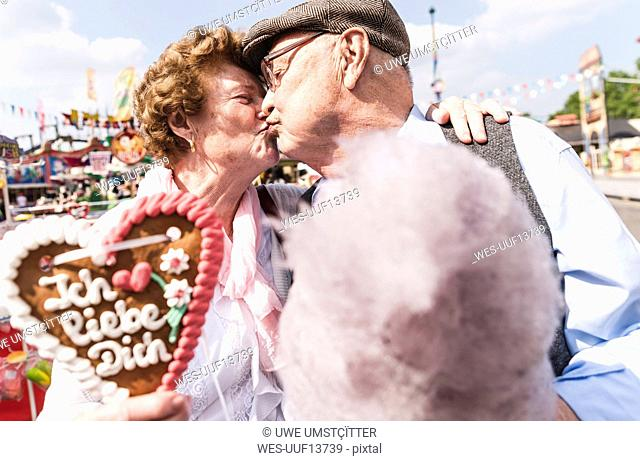 Senior couple with gingerbread heart and cotton candy kissing on fair