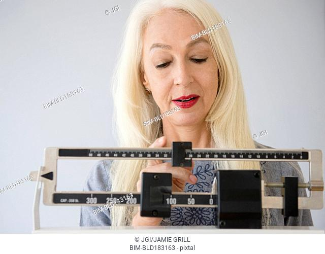 Caucasian woman weighing herself on scale
