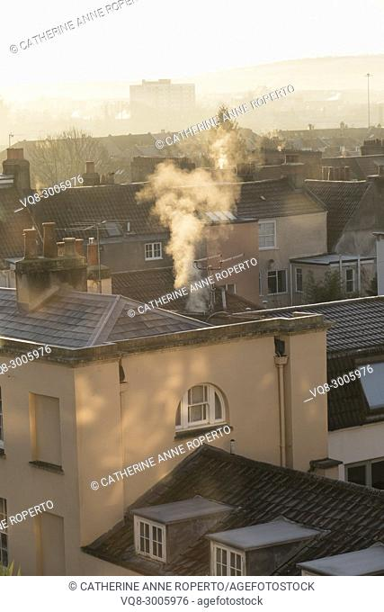 Dappled sunlight and plumes of white smoke curling upwards on a frosty day from the historic rooftops of Hotwells, Bristol, England
