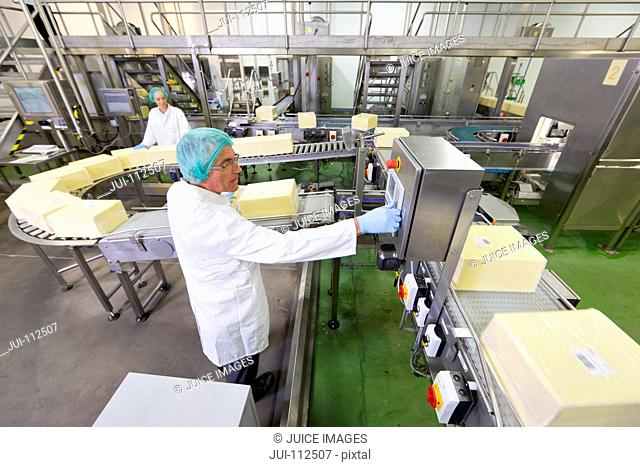 Worker at production line control panel in cheese processing plant