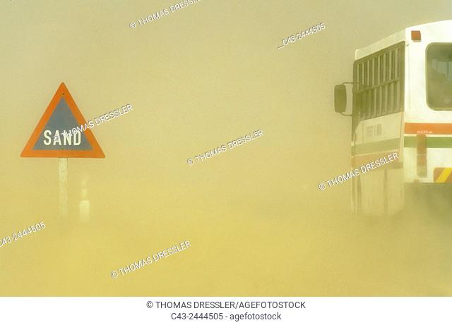 Sand road sign and sandstorm at the B 2 tarred road between Swakopmund and Walvis Bay in the Namib Desert. Namibia