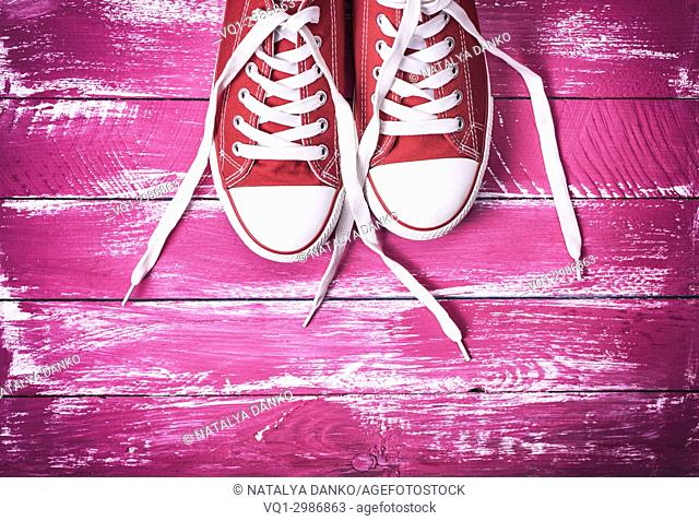 pair of red textile sneakers with white laces on a pink wooden background, top view