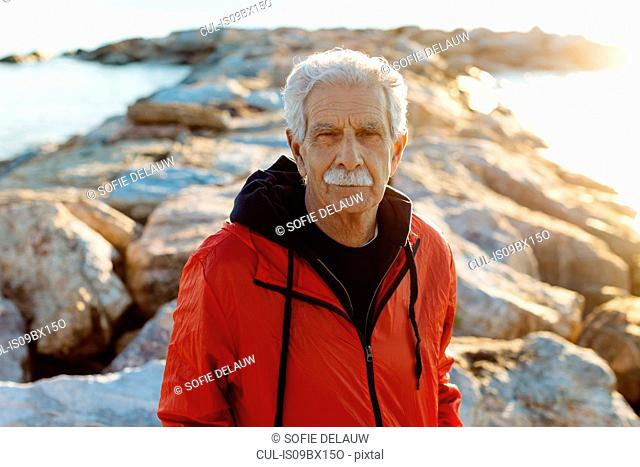 Portrait of senior man on beach, Livorno, Italy