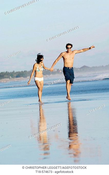 couple running and jumping on beach