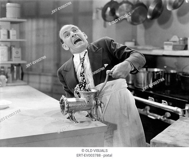 Man with tie stuck in meat grinder All persons depicted are not longer living and no estate exists Supplier warranties that there will be no model release...