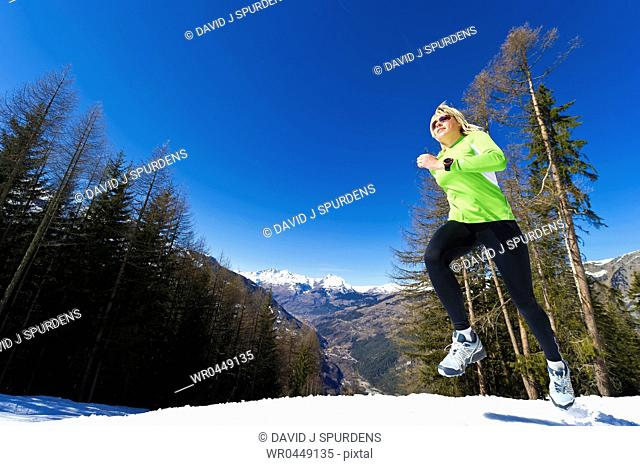 A woman jogging in snowy mountains