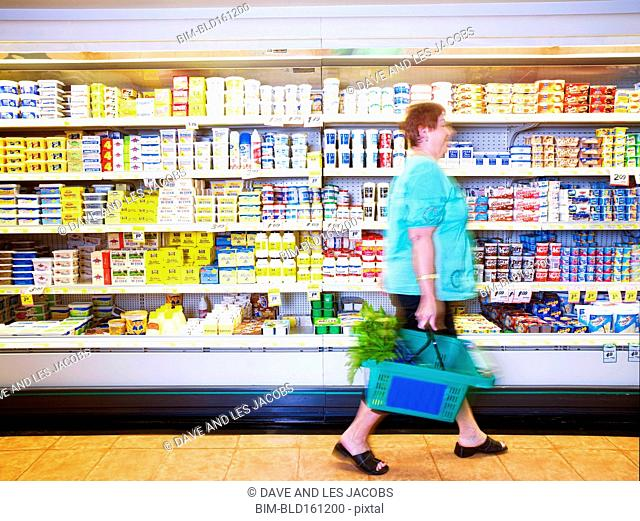 Hispanic woman carrying shopping basket in grocery store