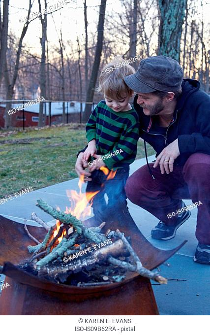 Boy and father tending fire in patio fire pit