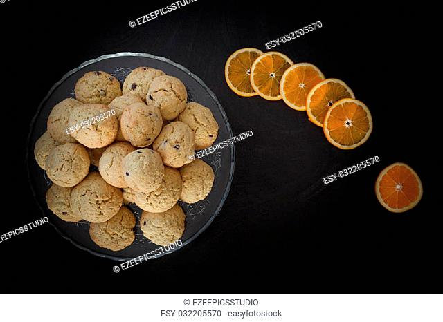 Top view of orange cookies on cake stand over black background with orange slices