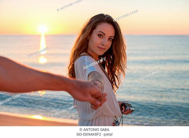 Young woman holding boyfriends hand at sunset on beach, Castiadas, Sardinia, Italy