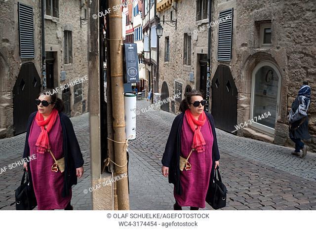 06. 06. 2017, Tuebingen, Baden-Wuerttemberg, Germany, Europe - A woman is reflected in a mirror as she walks along a cobbled alleyway in Tuebingen's old town