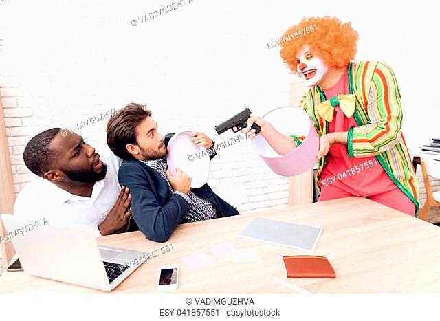A man in a clown suit is aiming a gun at businessmen in a bright office. He jokes on them on April Fool's Day. He has a cheerful mood