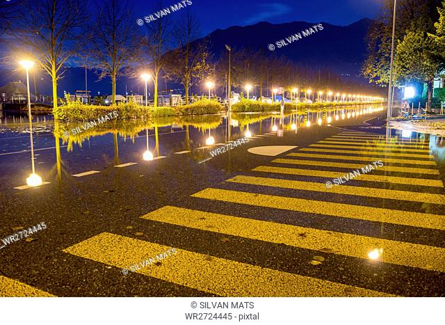 Flooding illuminated street in blue hour in Locarno, Switzerland