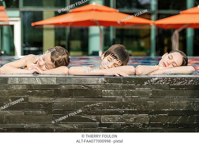 Siblings leaning on edge of swimming pool side by side, heads resting on arms